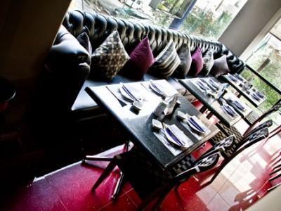 Sillones, mesas y alfombra morada de Sushi- Itto Tecamachalco